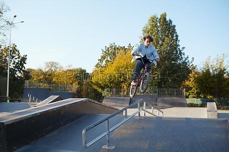 bmx biker rides by railing in