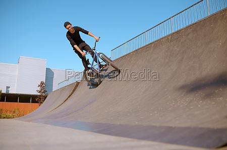 male bmx rider doing trick on