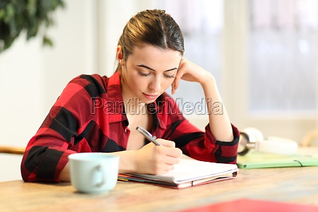 student studying taking notes at home