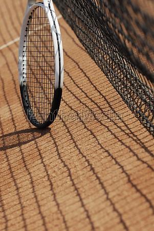 tennis racket near a tennis net