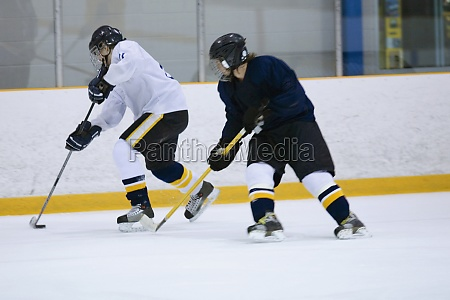 two ice hockey players playing ice