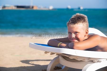blond boy lying on blue sun
