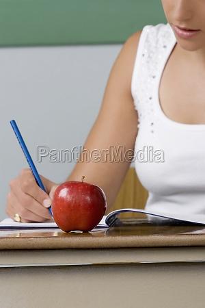 female teacher writing on a textbook
