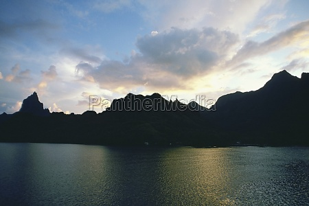 silhouette of hills at the water