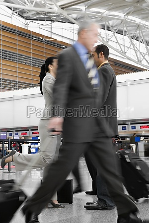 two businessmen and a businesswoman walking