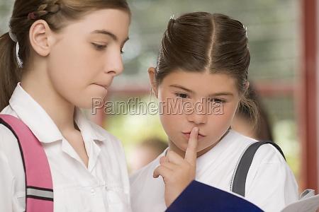 closeup of two schoolgirls looking at