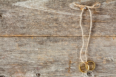 wedding rings hanging on wooden
