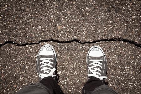 man standing on cracked asphalt floor