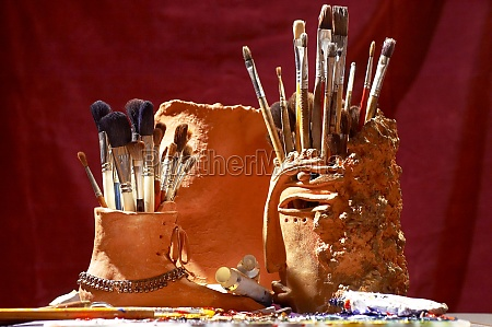 assortment of paintbrushes in holders