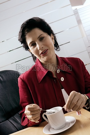 businesswoman dipping tea bag in a