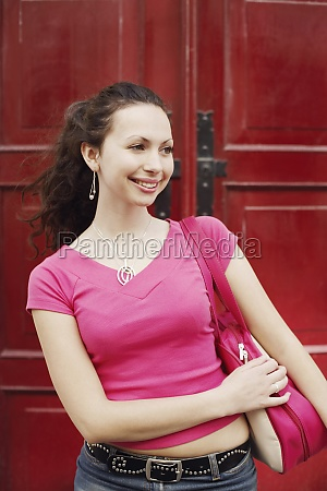 young woman carrying a bag on