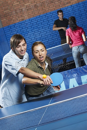young man teaching table tennis to