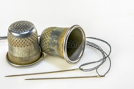 two thimble and two sewing needles