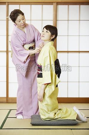 mature woman adjusting her daughterZs kimono