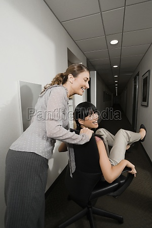 two businesswomen playing in an office