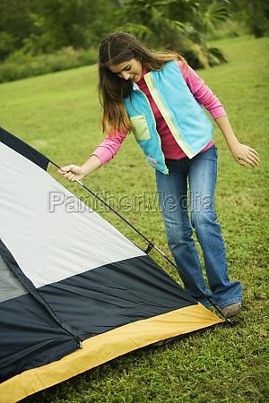 girl adjusting a tent