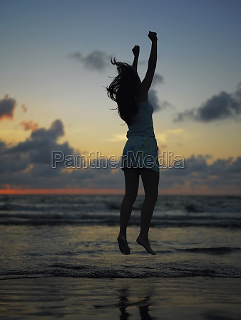 silhouette of a teenage girl jumping