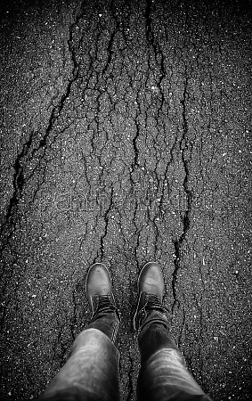 feet on cracked asphalt