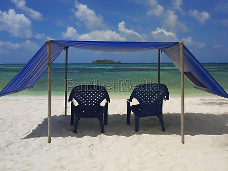 empty chairs under the tent on