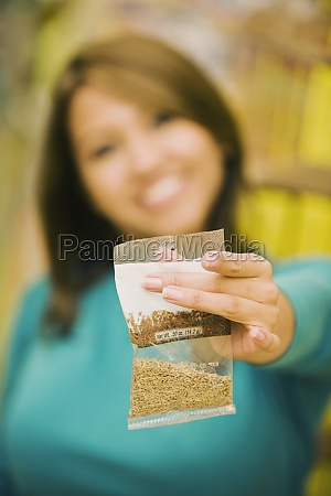 young woman holding a packet in