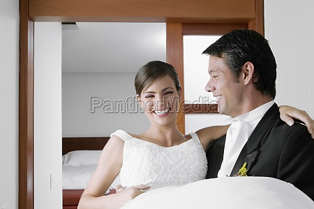 groom carrying his bride and smiling