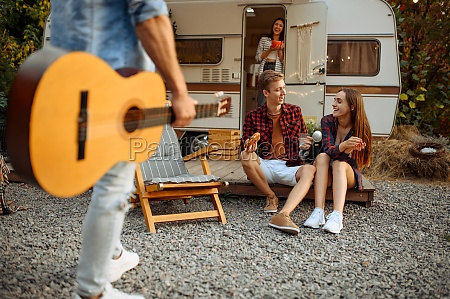 friends resting with guitar on picnic