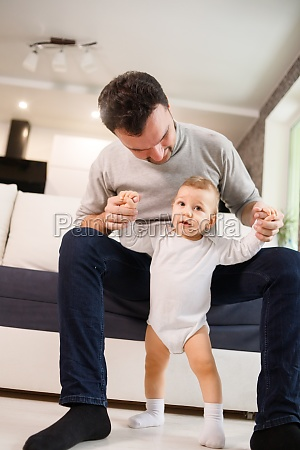 father teaching a baby to walk