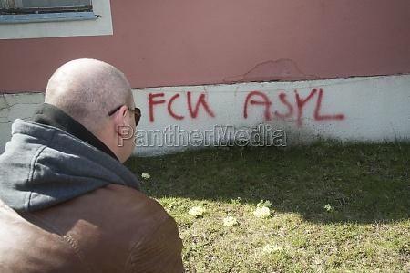man looks at a graffiti that