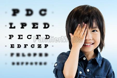 cute asian boy doing eye test