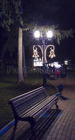 empty bench under lantern in evening