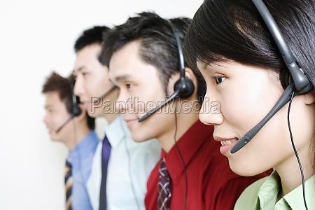 four customer service representatives talking on