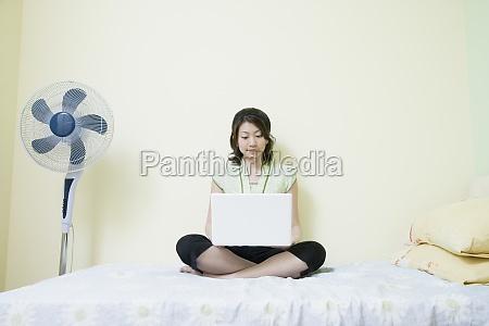 young woman sitting cross legged on