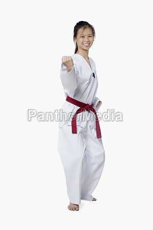 young woman practicing karate and smiling