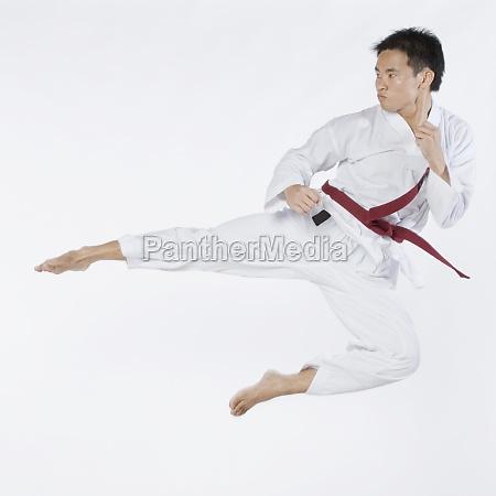 young man performing flying kick