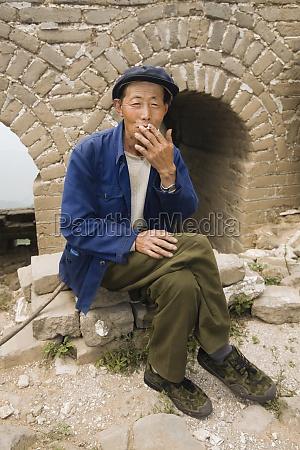 senior man smoking on a wall
