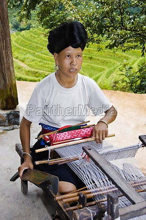 mature woman weaving a carpet jinkeng