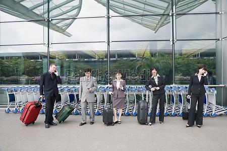 three businesswomen with two businessmen waiting