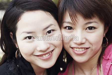 portrait of two young women cheek