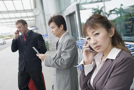 two businessmen with a businesswoman waiting