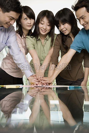 office workers stacking hands in an