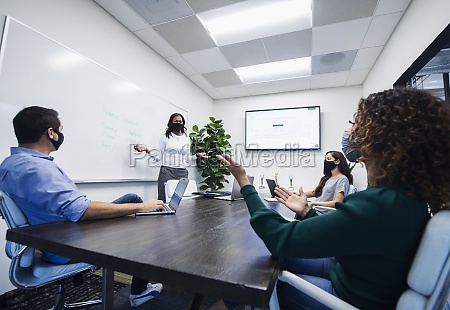 businesswoman in face mask giving presentation