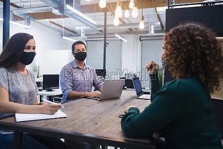 people in face masks having meeting