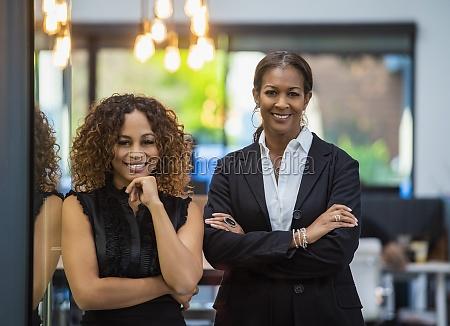 portrait of two smiling businesswomen standing