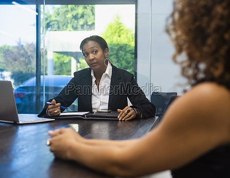 two businesswomen at conference table