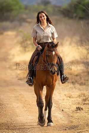 smiling brunette rides horse on dirt