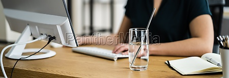 drinking glass on desk and woman