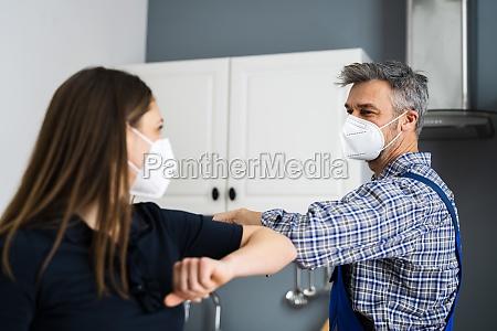woman elbow bump with repair man
