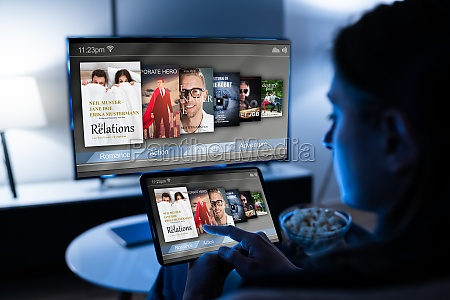 woman watching tv through tablet television