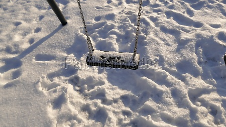 swing with snow cover in wintertime