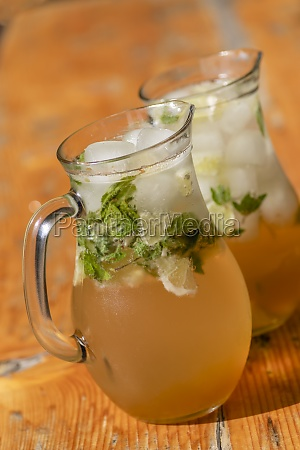 two mugs with mojito on wooden